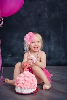 金髪の楽しい感情的な女の子のためのテーマの誕生日はピンク色でケーキを粉砕