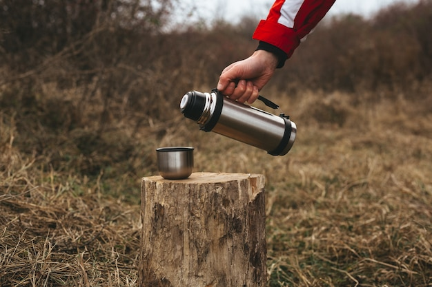 Themed trip. the man pours a hot drink into the thermos mug on a wooden log