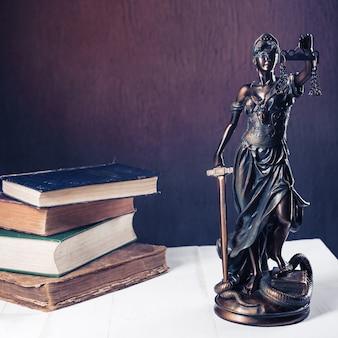 テミスの置物は、古い本の山の横にある白い木製のテーブルの上に立っています。法律弁護士のビジネスコンセプトをスケーリングします。 -画像