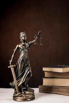 Фигурка фемиды стоит на белом деревянном столе рядом со стопкой старых книг. весы юрист бизнес-концепция. - изображение