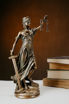 Themis figurine stands on a white wooden table next to a stack of old books