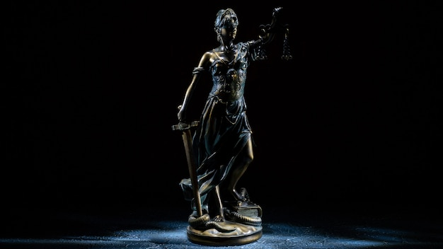 Themis statuette stands on the old vintage stone table