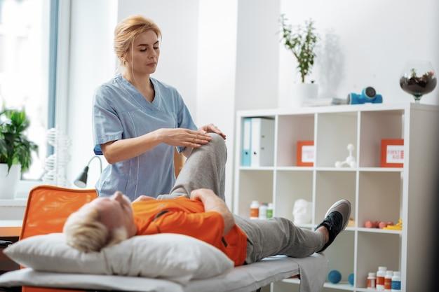 治療マッサージ。彼のためにマッサージをしている間彼女の患者の膝に触れる深刻な素敵な女性