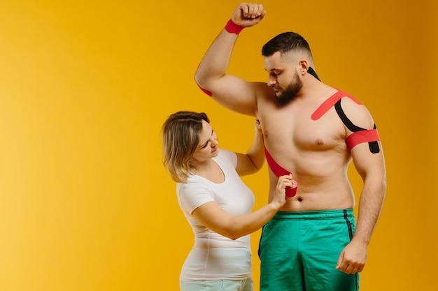 男の肩に治療テープ。運動学テープがどのように機能するかをアスリートに説明する女性医師。