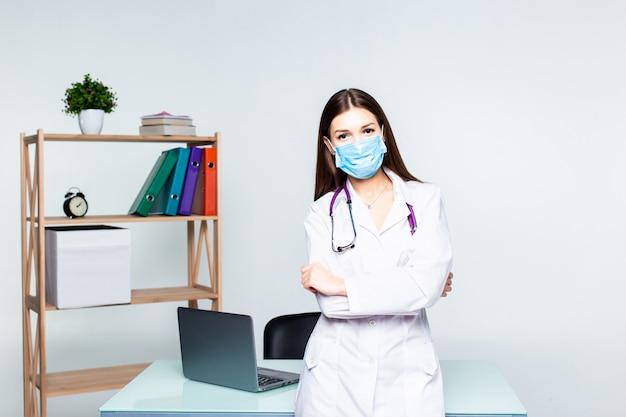 Портрет женского доктора therapeutist медицины стоя с руками пересек на ее комод держа стетоскоп в офисе. медицинская помощь или страховая концепция.
