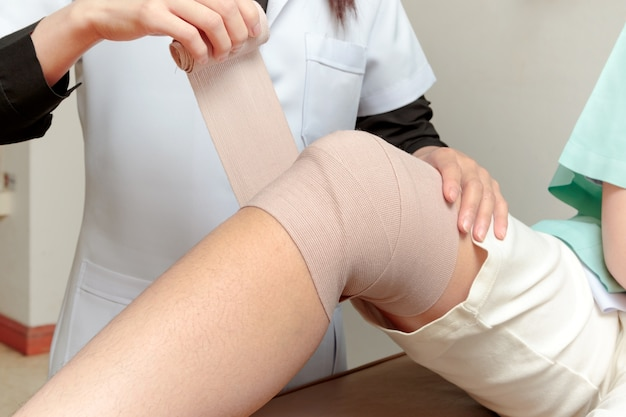 Therapist applying bandage on to patient's leg in clinic