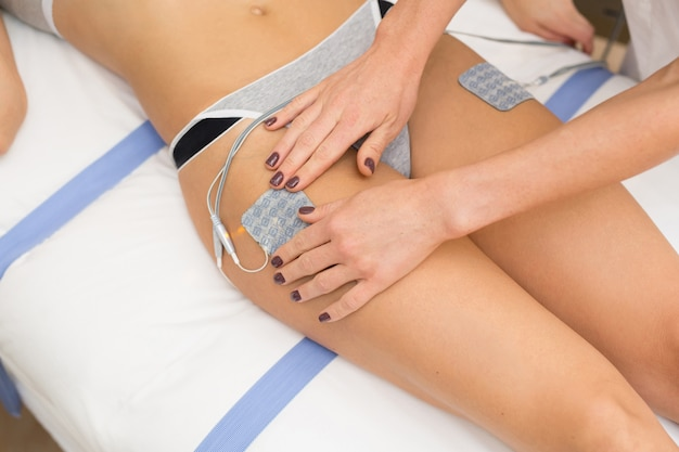 Therapist applying lipomassage on girls body in spa. close-up of biostimulating apparatus for anti-cellulite lipomassage. hardware cosmetology