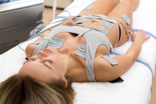 Терапевт, применяя липомассаж на теле девушки в спа. крупным планом - биостимулирующий аппарат для антицеллюлитного липомассажа. аппаратная косметология