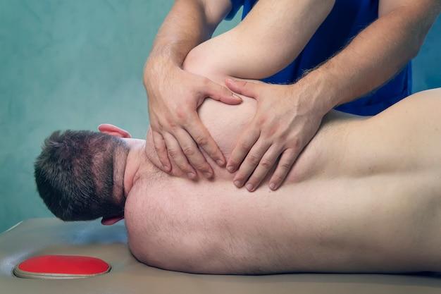 팔뚝으로 압력을 가하는 치료사. 남성 스포츠 마사지 치료사는 남성 경향이 있는 클라이언트에게 압력을 가합니다. 허리와 어깨 질환의 치료. 물리치료, 스포츠 부상 재활