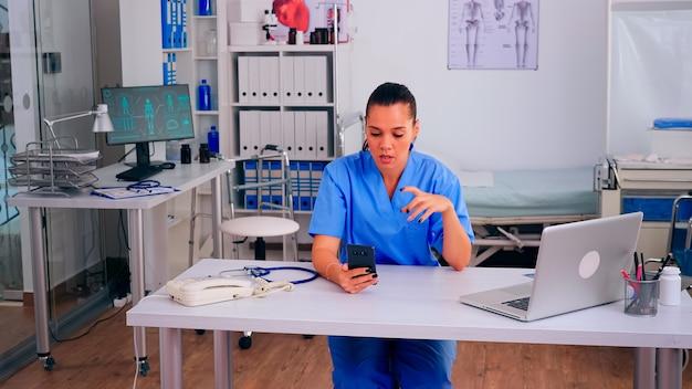 Ассистент терапевта, держащий смартфон, разговаривает с пациентом, совершающим телемедицинский онлайн-видеозвонок. удаленная консультация медсестры в приложении виртуального мобильного чата телеконференции, концерн телемедицины