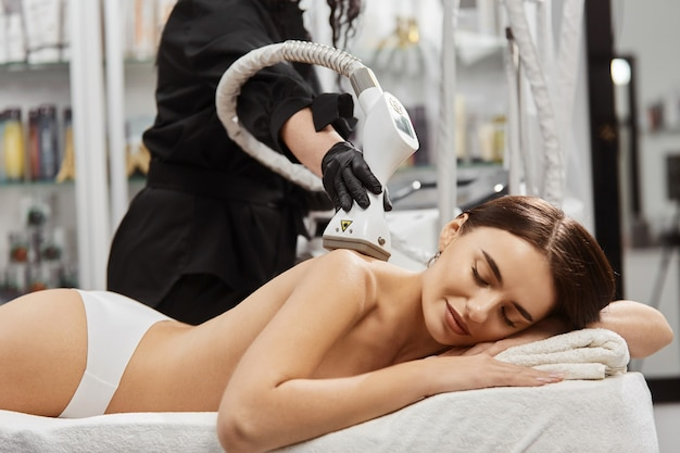 Therapist in black gloves holding massager on woman naked back