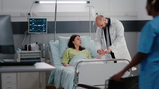 병원 병동에서 의료 상담 중 심장 박동을 분석하는 치료사