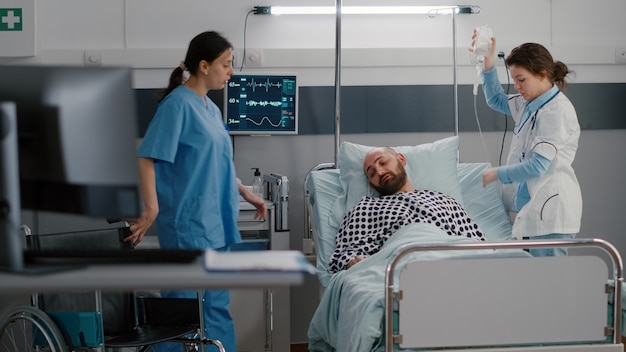 Therapist doctor analyzing heart pulse during respiratory expertise in hospital ward. medical nurse putting sick patient in wheelchair for physiotherapy consulting recovering after leg accident