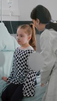 聴診器を患者の胸に当てて心拍を聞いている病気の子供に相談するセラピスト医師