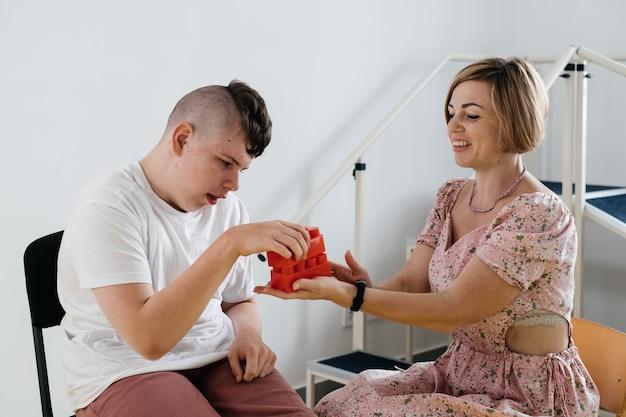 大脳性麻痺の少年と開発活動をしているセラピスト