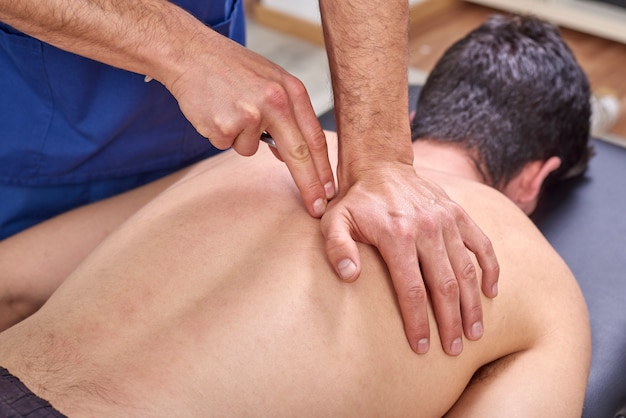 Therapist doing diacutaneous fibrolysis, of the hooks healing treatment on man's back