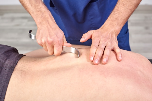 Therapist doing diacutaneous fibrolysis, of the hooks healing treatment on man's back.
