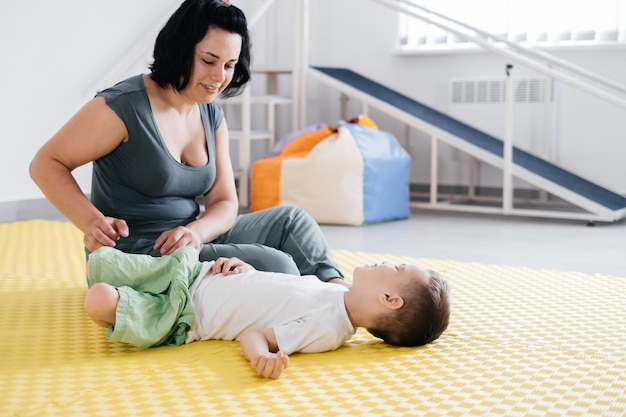 障害児と一緒にマットの上でエクササイズをしているセラピスト
