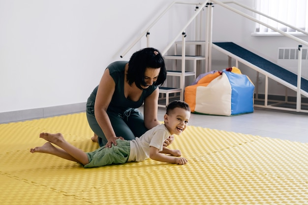 大脳性麻痺児のリハビリを行うセラピスト Premium写真