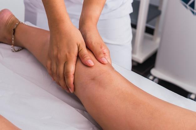 스파 센터에서 여성에게 종아리 마사지를 하는 치료사. 마사지는 스파 살롱의 마사지 테이블에 있는 여성의 다리를 마사지합니다.