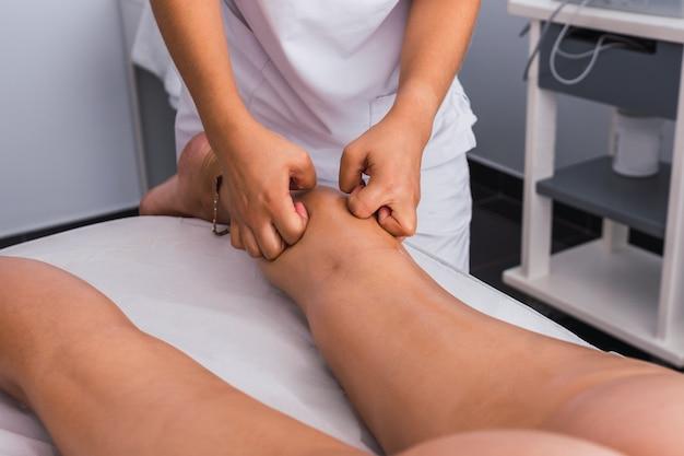 Терапевт делает массаж икр женщине с костяшками пальцев в спа-центре. массажистка массирует ногу женщины на массажном столе в спа-салоне.