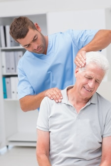 Therapist giving massage to senior male patient