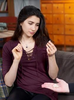 Терапевт дает таблетки пациентке молодой женщины во время сеанса терапии