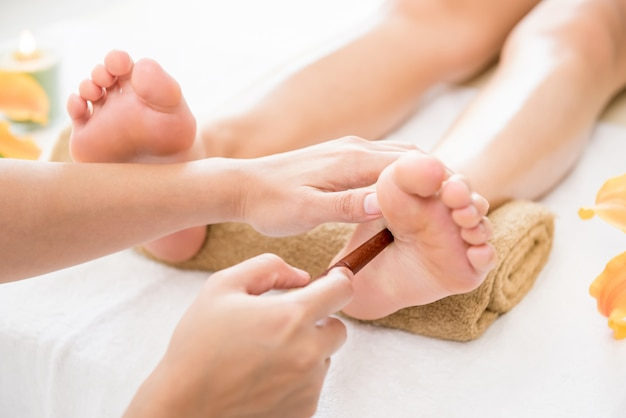 Therapist giving reflexology relaxing traditional thai spa foot massage with stick