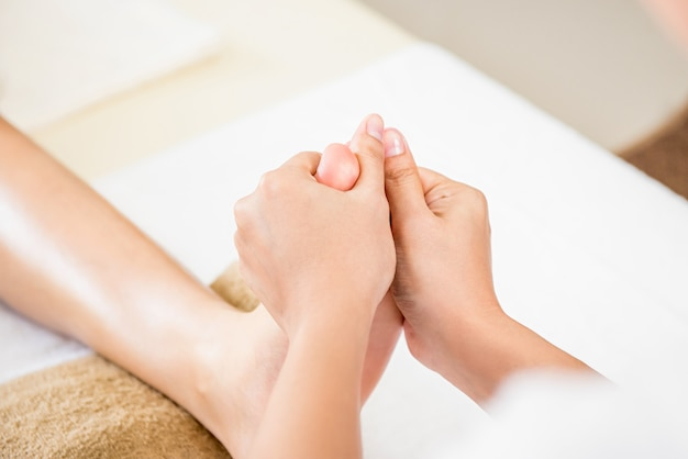Therapist giving relaxing reflexology thai foot massage to a woman in spa