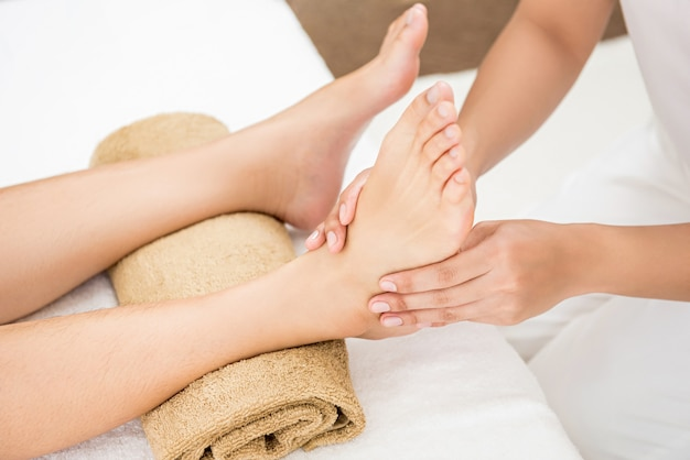 Therapist giving relaxing thai reflexology foot massage to a woman in spa