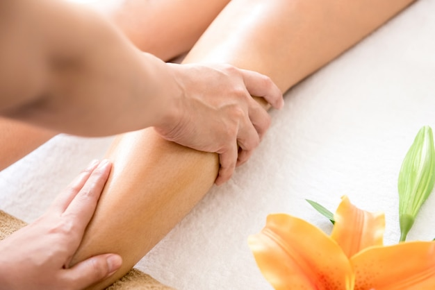 Therapist giving thai oil leg massage treatment to a woman in spa