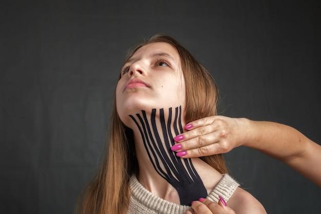 치료사 손은 어린 소녀의 목에 운동 요법 테이프를 적용하고 있습니다.