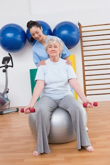 Therapist helping senior woman fit dumbbells on exercise ball