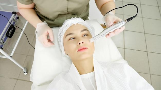 滅菌手袋を着用したセラピストが、医療美容クリニックの女性訪問者の顔にマイクロダーマブレーション装置を移動します。
