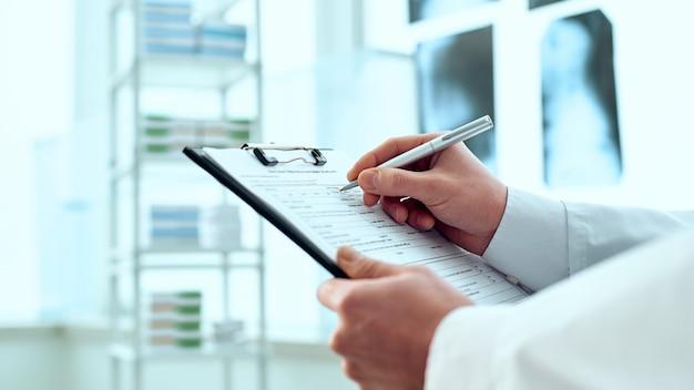 Терапевт делает запись в регистрационной карточке пациента
