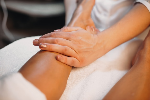 Therapist is massaging the client's legs during a skin care procedure