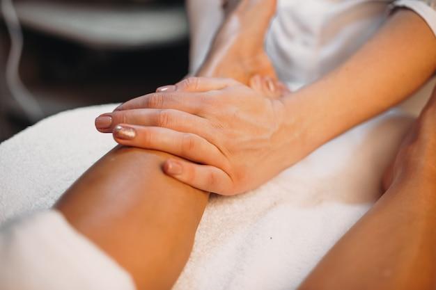 치료사는 피부 관리 절차 중에 고객의 다리를 마사지하고 있습니다.