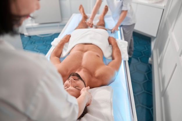 Therapist massages head of man while young colleague works with his legs in hospital