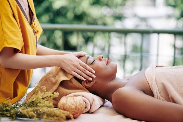스파 리조트에서 편안한 젊은 아름 다운 아프리카 계 미국인 여자의 머리와 얼굴을 마사지 치료사