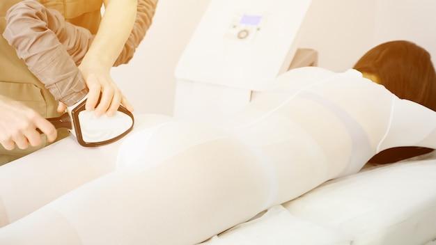 Терапевт перемещает механическое устройство липомассажа на пациента
