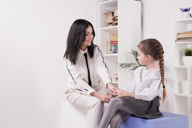 セラピストセッションのコンセプト。かわいい小さな子供と一緒に働く女性心理学者。