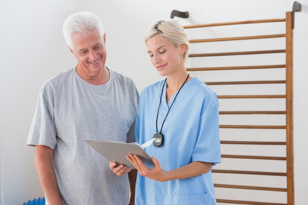 Therapist showing clipboard to senior man
