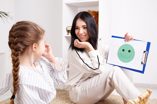 종이에 웃는 얼굴을 작은 환자에게 보여주는 치료사. 심리학자 개념입니다.