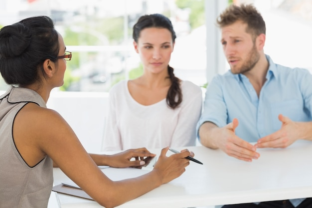 机に座っているカップルと話すセラピスト