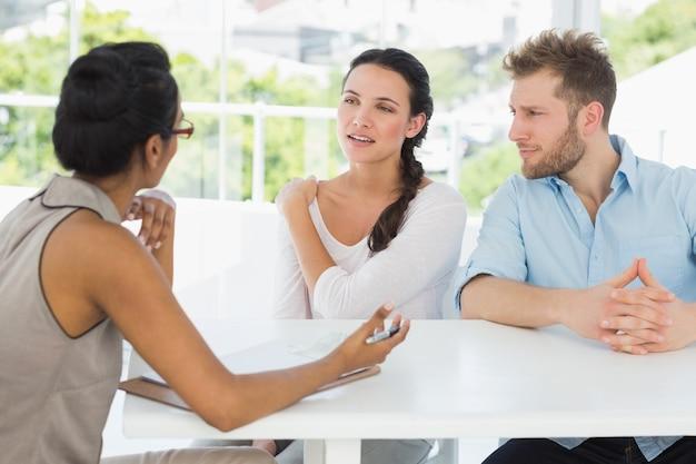 セラピストが机に座っているカップルと話す