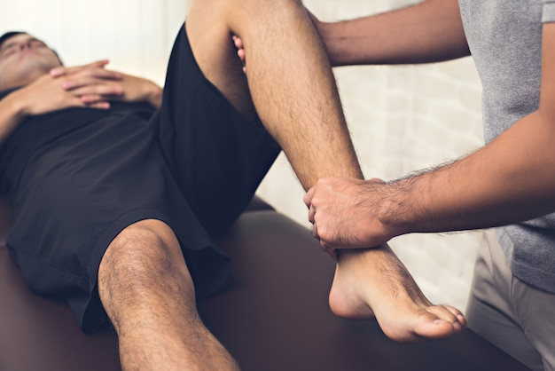 Therapist treating injured leg of athlete male patient in clinic