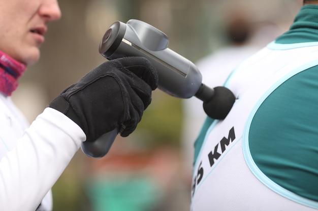 Терапевт лечит травмы человека массажный пистолет, используемый профессионалами для массажа тела концепция спортивной физиотерапии