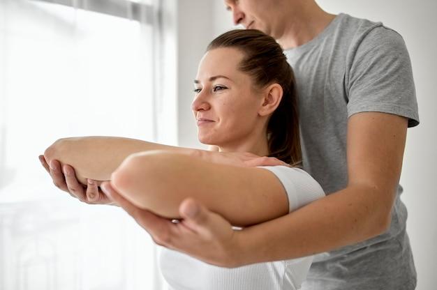 여성 환자와 물리 치료를 받고있는 치료사