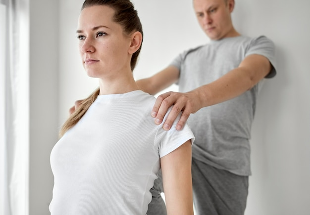 Therapist undergoing physical therapy with female patient