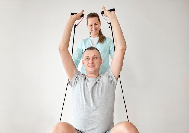 남성 환자와 물리 치료를 받고있는 치료사